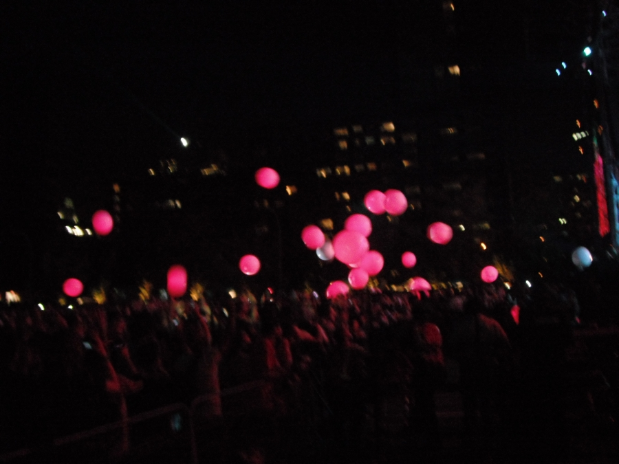 Inflatable balls shine pink as they're tossed in the air above the crowd
