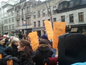 women hold orange placards outside Montreal courthouse