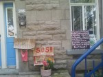 Protest signs in front of door, in window of a house.