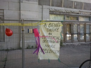 Sign hanging on fence in front of Empress building