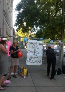Women blow up balloons and pink flamingoes around protest sign on fence