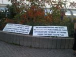 "Protest signs in French and English lie side by side on grass. Text of English sign says: ""NDG gets construction and traffic. We want bike paths, pedestrians and parks. Applebaum and Tremblay: Defend NDG. Change the MUHC Traffic Plan"