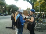 Marlo Turner Ritchie chats with a woman rally participant. Both are wearing bicycle helmets