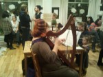 A harpist plays as people chat at Le Milieu launch party