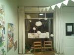 Tissue paper flowers hang in window below paper banners