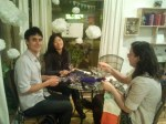 "One man and two women sit at table ""yarnbombing"" at Le Milieu launch party"