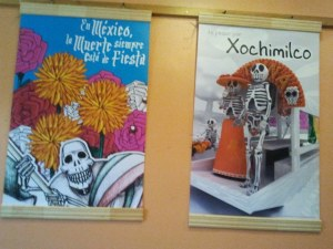 two of Mexican day of the dead posters hanging on wall at Cafe 92 degrees