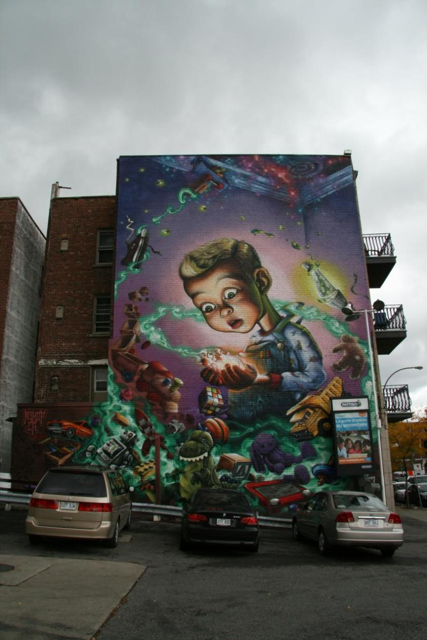 Huge wall-length mural of child with a galaxy of toys at corner of Décarie & Sherbrooke
