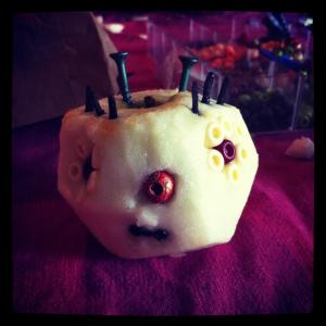 screw-head halloween decoration pumpkinlike apple?  with beady eyes and screws sticking out