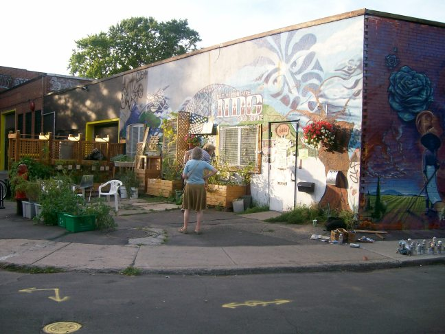 photo of NDG Food Depot, Oxford side, withwoman looking at wall mural, outdoor patio in view