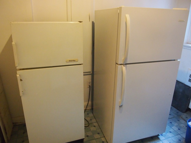 two white fridges, one small, one large, side by side
