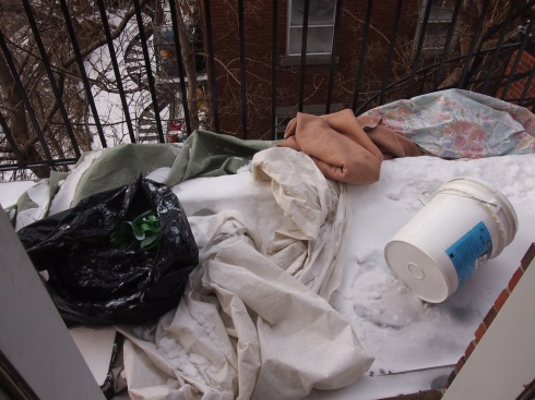 Not so welcoming: painters' drop cloths, garbage and a paint bucket on our new back balcony