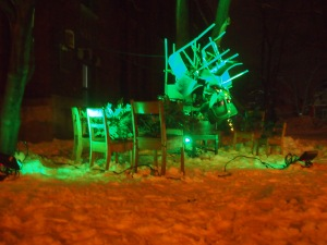 the green classroom - chairs, evergreen sprigs and a watering can lit up in green