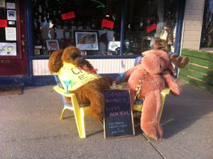 George the orangutan and Mortimer the moose sit with martini glasses in chairs outside Cartes Etc.'s store
