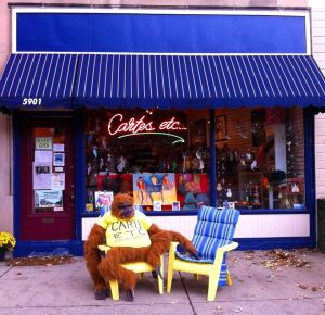 George the orangutan wears a Cartes etc. t-shirt as he sits in a chair outside in front of the store