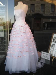 white dress adorned with donors's names in black writing on pink pieces of paper or fabric