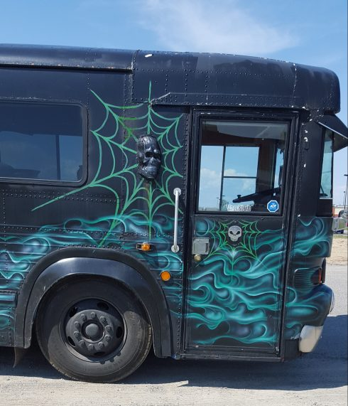 Close up of the bus with its black background, painted teal-green smoke and green cobwebs, superimposed cast-iron effect skull and silver skull details