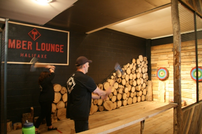 A woman and man throw axes towards colourful wooden targets at Halifax's Timber Lounge