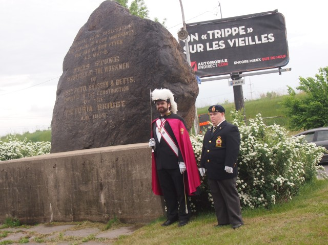 A colourfully dressed member of the Knights of Columbus stands beside a Canadian soldier next to the Black Stone on May 29, 2016